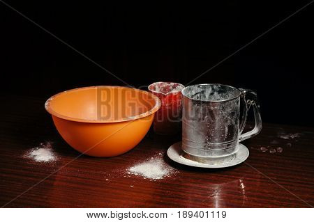 Orange cup measuring cup and a steel sieve stand on a wooden table on a black background. Flour.