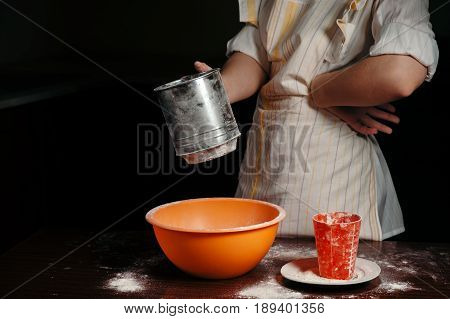 The girl sifts the flour in a steel sieve. Bright kitchen items.