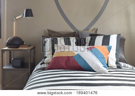 Wooden Reading Lamp On Bedside Table Next To Striped Bedding Style In The Bed Room