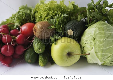 Green vegetables lettuce herbs and fruits at border of image with copy space for text. Cabbage zucchini cucumbers radish tomatoes kiwi spinach parsley mints and lettuce. Vegetables and fruits on a white background.