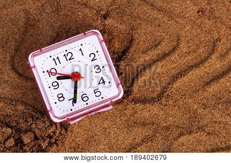 Alarm clock in the sand, object on the beach