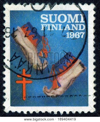 MOSCOW RUSSIA - 03 June 2017: A Postage stamp printed by Finland shows traditional finnish shoes circa 1967