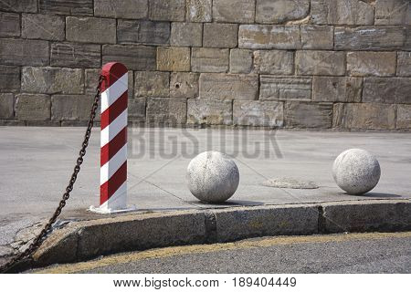 Photo of a bollard and two stone balls with sunlight