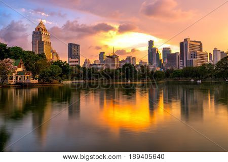 Sunset scence of Bangkok skyline Panorama Aerial view of Bangkok modern office buildings and condominium in Bangkok city downtown with sunset sky and clouds at Bangkok Thailand. Reflection on Lake