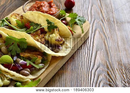 Tacos tortilla with roasted cauliflower beans vegetables and sauce, space for text