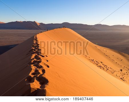 People watching sunrise form the Dune 45 in the Sossusvlei area of the Namib Desert in Namibia.