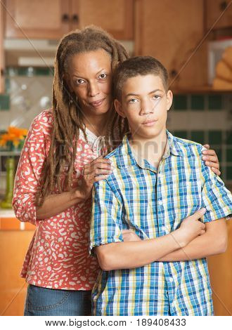 Disagreeable Teen Boy Stands Grimacing Beside His Loving Mother