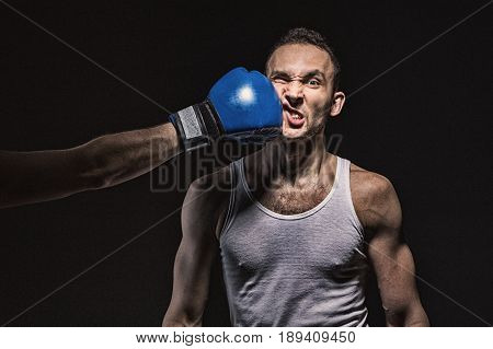 Boxing kick in the face on black background