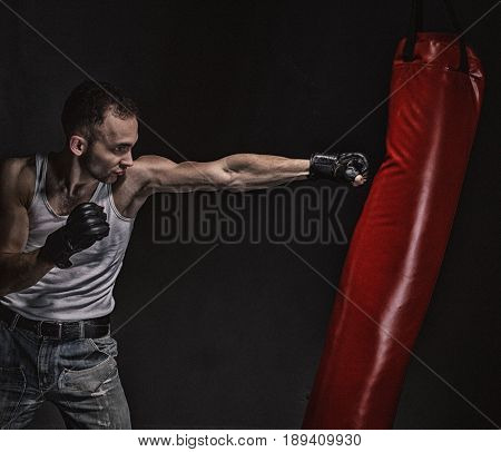 Boxing kick in the boxing bag on black background
