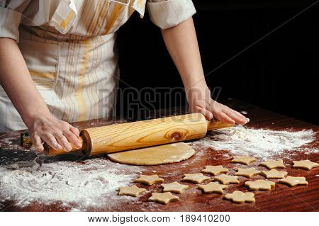 A woman in the kitchen is rolling a dough on a wooden table with a wooden rolling pin. She molds cookies in the form of asterisks.