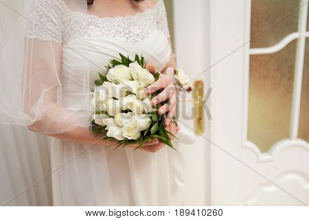 Wedding bouquet of white roses and green leaves in bride's hands.