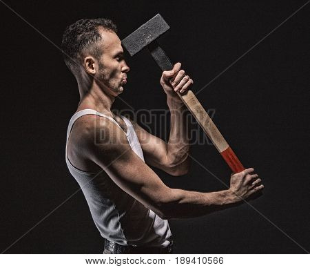 Man hits himself with hammer on black background