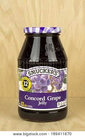 RIVER FALLS,WISCONSIN-JUNE 03,2017: A jar of Smucker's brand concord grape jelly with a wood background.