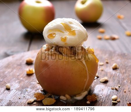 Baked apple stuffed with granola decorated with ice cream close up view