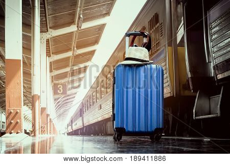 summer dayBlue luggage and hat white on floor at platform of railway station. travel concept.