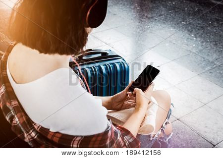 hipster girl luggage and using smartphone at the train station with a traveler. Travel concept.