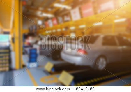 Blurred background of technician repairing the car in garagemechanics fixing in a workshop suspension detail of lifted automobile at service station. Public service garage in thailand.