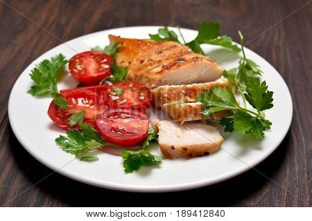 Dinner with sliced roasted chicken breast and vegetable salad. Shallow depth of field