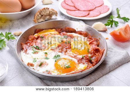 Morning food. Fried eggs with tomatoes and bacon in frying pan
