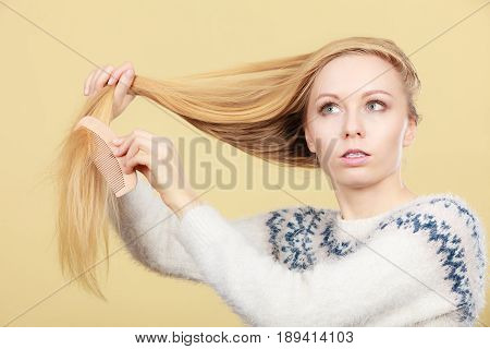 Haircare choosing best conditioner for tangled hairstyle concept. Teenage blonde girl brushing her hair with comb