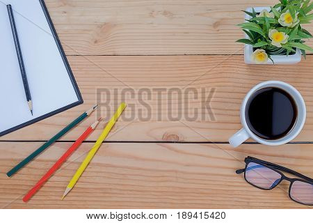 Office desk table with keyboard notebook pen cup of coffee and flower. Top view with copy space. (selective focus)