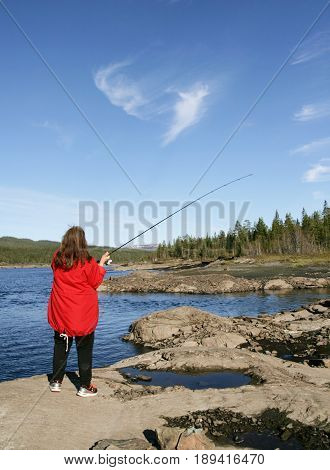 Woman fishing by a lake in a rocky landscape