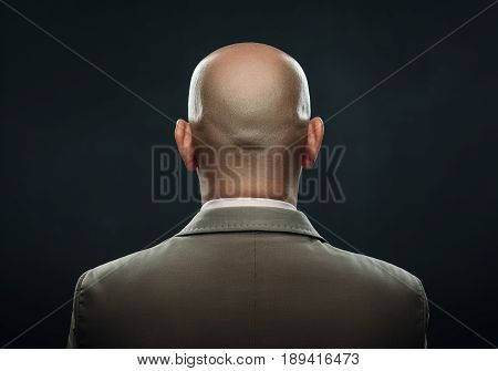 Nape of bald man in suit against a dark background