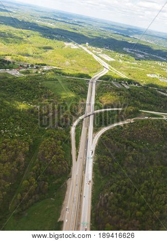 Aerial view of farm land and interstate highway through the clouds