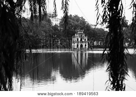 Hanoi, Vietnam. Turtle Tower at Hoan Kiem Lake in Hanoi, Vietnam. Tree at the foreground, cloudy moody weather. Black and white