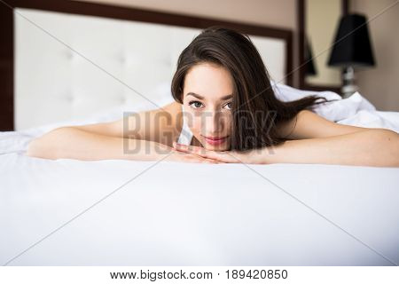 Woman Lying At The End Of The Bed Underneath The Quilt And Smiling, With Her Head Resting Upon Her H