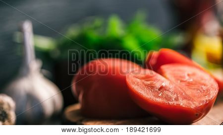 Fresh heart-shaped tomato on cutting board with garlic and green potherbs. Close-up. Vegetarian concept