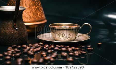 Roasted coffee beans scattered around cup off coffee and copper coffee pots on reflective glossy black background. Selective focus