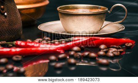 Roasted coffee beans scattered around copper cup off coffee and coffee pots on reflective glossy black background with red chili peppers. Selective focus