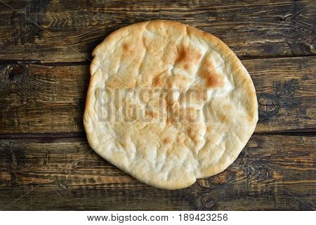 Naan bread on wooden background top view