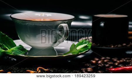 Tea in white cup with fresh mint and coffee in black cup with red chili peppers on glossy black background covered with dried black tea and roasted coffee beans. Selective focus