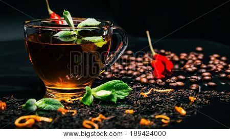 Black tea in transparent cup with fresh mint and red chili peppers on glossy black background covered with dried black tea and coffee beans. Selective focus