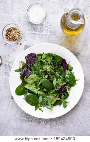 Healthy natural green salad with leaves of spinach arugul on light background. Top view