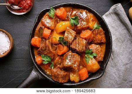 Goulash beef stew in cast iron pan top view close up