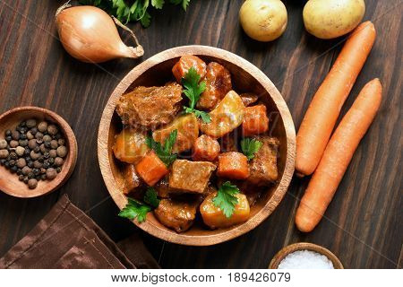 Meat stew with vegetables in bowl on wooden background top view