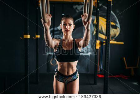 Slim female athlete training on gymnastic rings