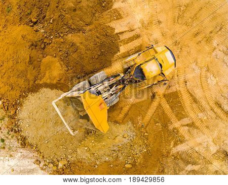 Aerial view of truck on muddy road on a construction site. Heavy industry from above. Industrial background from devastated landscape.