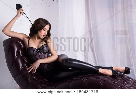 Sexy elegant woman lies in a corset on a leather sofa. Sensual woman posing on couch
