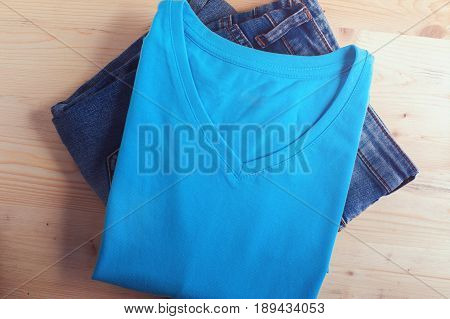 Blue t-shirt and denim jeans on wooden table. Male casual cloth. Fashion, clothing background.