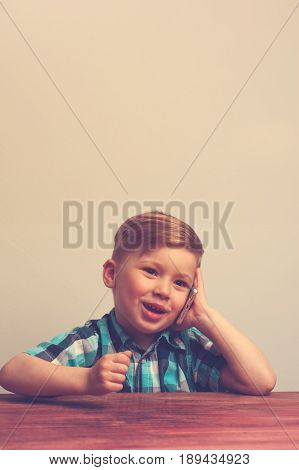Portrait of little caucasian boy with smartphone. Cute child sitting at the table and talking on the phone. Modern digital gadget in child's hands.