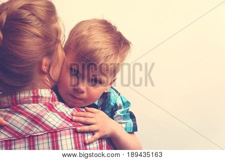 Cropped shot of little caucasian boy hugging his mother after sorrow at home. Young woman comforting her little child. Family relations concept. Copyspace