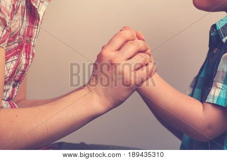 Closeup of woman's and child's hands. Mother and son holding hands. Family relations concept.