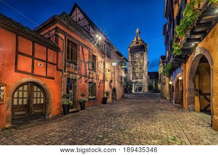 Evening street with Dolder Tower and traditional colorful half-timbered houses in Riquewihr village on alsatian wine route Alsace France