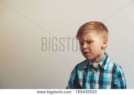 Portrait of unhappy and tired caucasian child on white background. Frustration and depression.