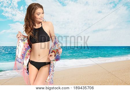 Young woman in stylish swimsuit relaxing on beach. Fashion and summer vacation