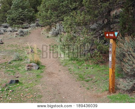 A sign marks the trailhead at Chimney Rock which is a rugged trail with lots of rocks, juniper trees, and sagebrush near the Crooked River in Central Oregon on a spring day.